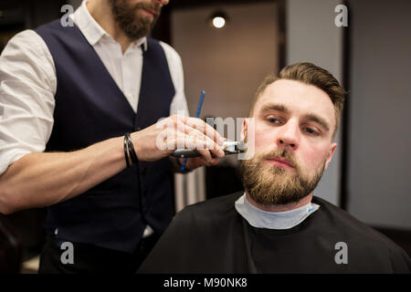 Portrait of barber trimming young man - Stock Photo