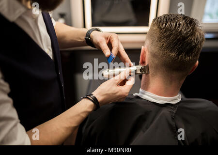 Back portrait of man being trimmed at barber shop - Stock Photo