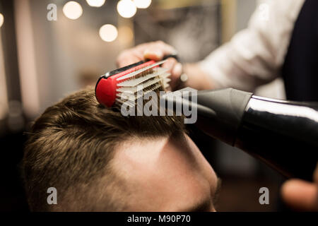 Close up portrait of hairdresser styling customer hair - Stock Photo