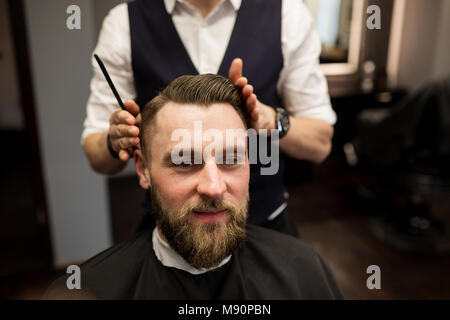 Portrait of happy man having hair cut at barber salon - Stock Photo