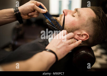 Profile portrait of young man having beard trimmed at barber salon - Stock Photo