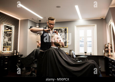 Profile portrait of smiling man having hair cut in salon - Stock Photo