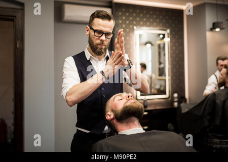 Portrait of barber rubbing foam in hands before shaving - Stock Photo