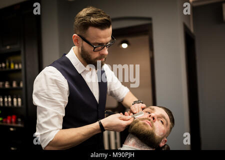 Portrait of barber shaving customer with razor - Stock Photo