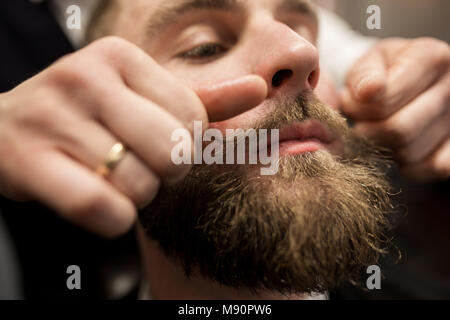 Close up portrait of bearded man having mustache curling up - Stock Photo