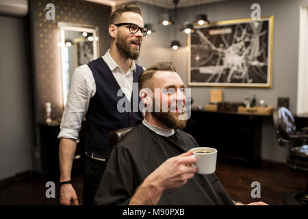 Portrait of happy barber and customer drinking coffee in salon - Stock Photo