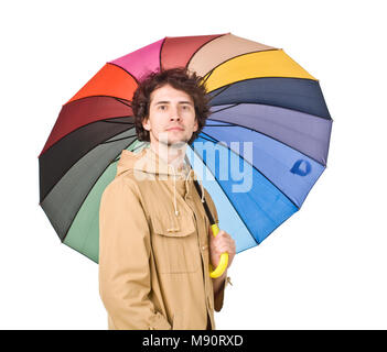 Young man wearing in raincoat posing with umbrella - Stock Photo