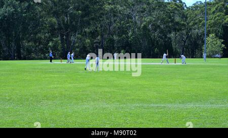Dated 20 Mar 2018. Cricket match played on ground in Coffs Harbour, New South Wales, Australia. Wide shot of unidentifiable cricketers playing cricket - Stock Photo