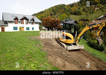 Construction site.  Mechanical digger at work in a garden. - Stock Photo