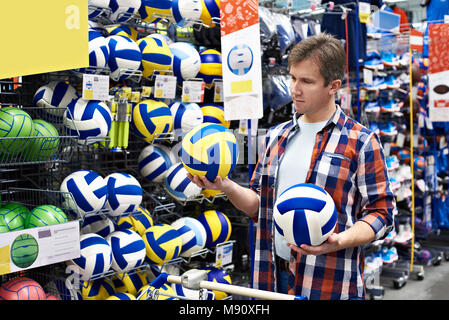 Man chooses volleyball in the sports shop - Stock Photo