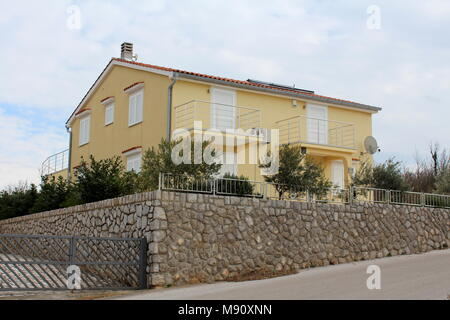 Modern Mediterranean villa closed for winter with air conditioner and satellite dish in front, solar panels on roof and surrounded with traditional st - Stock Photo
