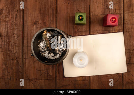 An overhead photo of a witch's cauldron, an open grimoire with blank pages, and candles. Wiccan ritual objects, shot from above on a dark background w - Stock Photo