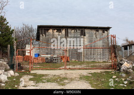 Old wooden warehouse building with building material and uncut grass behind locked rusted metal fence doors on cold winter day - Stock Photo