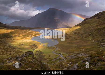 Rainbow passing over Cwm Idwal in the mountains of Snowdonia National Park, North Wales. Autumn (September) 2017. - Stock Photo