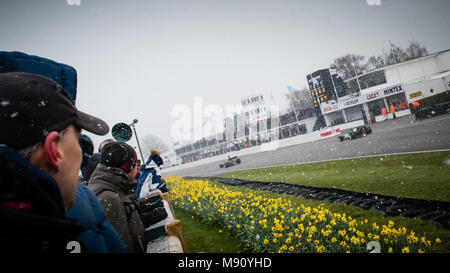 Formula 5000 racing cars go past the Pit Lane in the snow during the 2018 Goodwood Members Meeting 76MM demonstration drive. - Stock Photo