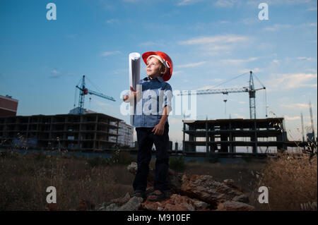 cute caucasian little boy in helmet with paper of draft in his hand on construction site with crane and new buildings - Stock Photo