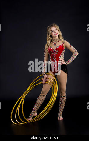 The contortionist girl in stage costume with hoops. Studio shot on dark background. - Stock Photo