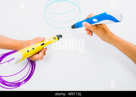 Kids hands holding 3d pens with filaments on white background. Top view - Stock Photo