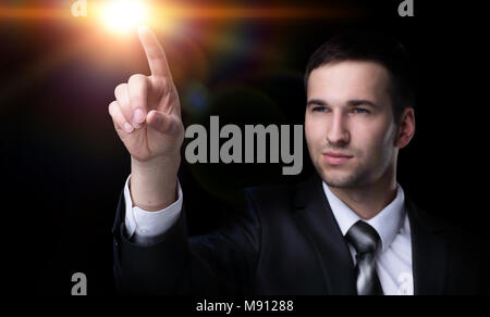 Business man pressing an imaginary button. Isolated on black. - Stock Photo