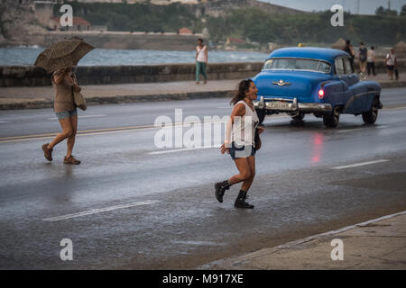 Two adult females crossing a rain soaked  Malecon one carrying umbrella as blue Cuban classic car passes by, Havana, Cuba, Caribbean - Stock Photo