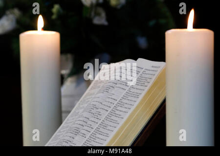 Church candles and open  bible on an altar.  Strasbourg. France. - Stock Photo