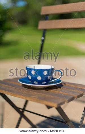 Large blue cup with white polka dots on folding wood and metal bistro chair in a secluded garden on a sunny day. - Stock Photo