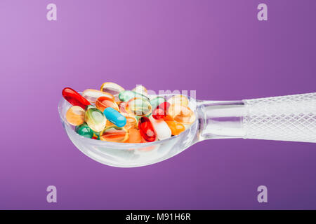 close up view of medicines in spoon isolated on purple - Stock Photo