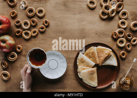 cropped shot of person drinking tea and eating pancakes at wooden table - Stock Photo