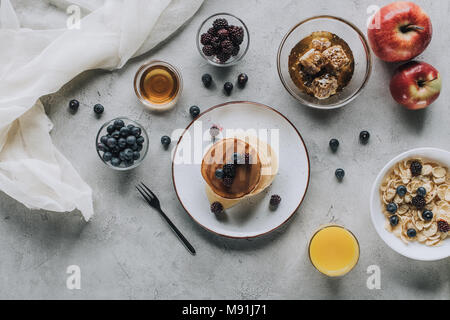 top view of healthy breakfast with homemade pancakes, fresh fruits and honey on grey - Stock Photo