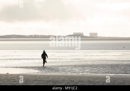 A youth running across sands at low tide at Jenny Brown's Point near Silverdale UK with Heysham Nuclear Power station in the distance. January 2018 UK - Stock Photo