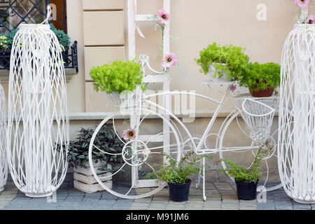 Decorative white iron bicycle stand for plants and flowers, street, decor - Stock Photo