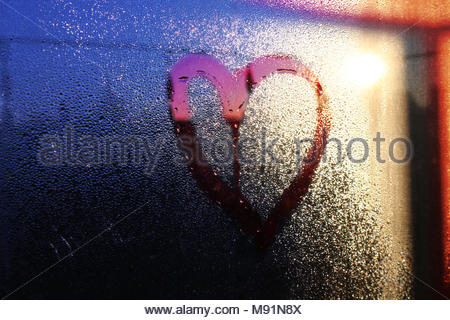 Heart drawn on water dew drops on glass window - Stock Photo