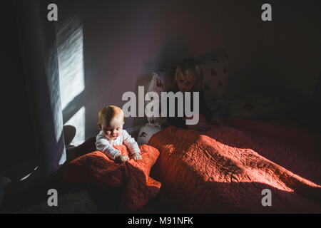 baby in babydoll cradle dramatic light trendy kids room - Stock Photo