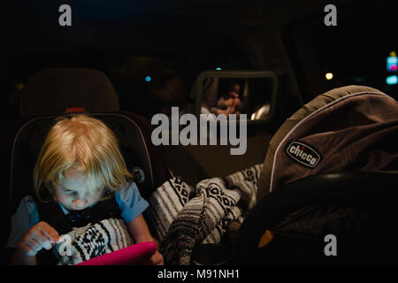 girl plays on ipad tablet in backseat while baby sleeps in carseat night time - Stock Photo