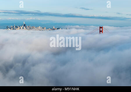 View of the Far Golden Bridge Far Red Tower next to San Francisco Sky Scrappers with Dense Clouds Moving in - Stock Photo