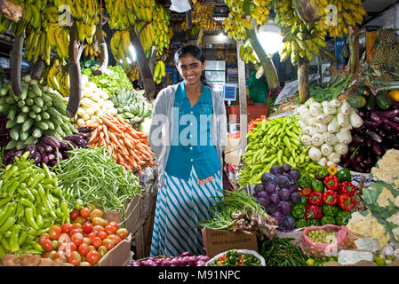 A young Sri Lankan woman trader at her colourful vibrant stall in the Central Market of Nuwara Eliya selling fresh homegrown fruit and vegetables. - Stock Photo