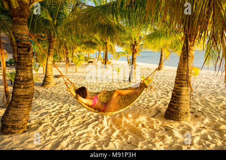 Woman relaxing at sunset in a traditional hammock between palm trees - Stock Photo