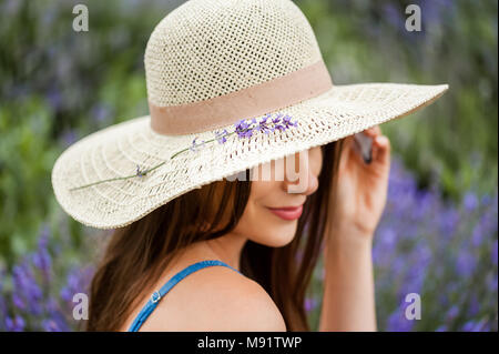 Young woman surrounded by lavender plants wearing a straw hat looking beautiful. - Stock Photo