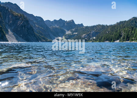 Pristine alpine mountain lake in summer surrounded by evergreen pine tree forest mid day sun close up low angle water. - Stock Photo