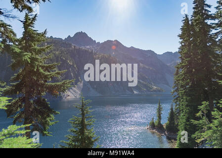 Pristine alpine mountain lake in summer surrounded by evergreen pine tree forest late day sun rays. - Stock Photo