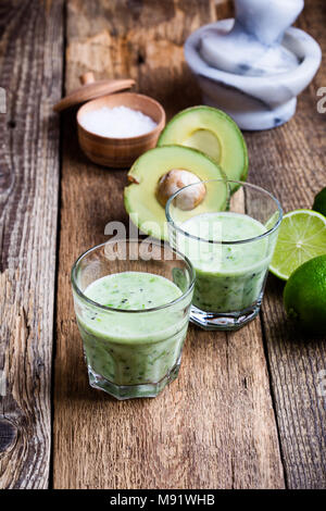 Guacamole dip style green vegetables smoothie in glasses with ingredients avocado and lime on rustic wooden table, savory healthy dairy drink with org - Stock Photo