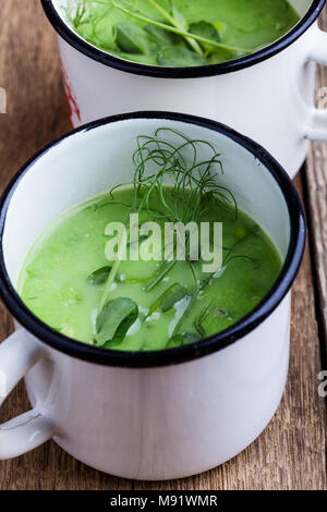 Cream soup with green pea, fresh herbs and sprouts with micro greens on top in rural mugs, healthy vegetarian meal - Stock Photo