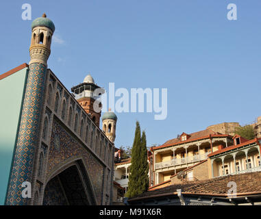 The blue-tiled facade of Orbeliani Baths, red-brick minaret of a mosque, balconied homes in Old Town, and Narikala Fortress on hill, Tbilisi, Georgia - Stock Photo