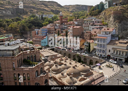 The Abanotubani, Orbeliani Baths, red-brick minaret of a mosque, balconied homes in Old Town, Narikala (Nariqala) Fortress on hill, Tbilisi, Georgia - Stock Photo