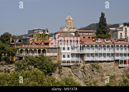 The Hotel Old Metekhi on a rocky cliff above the Mtkvari River with Tsminda Sameba (Holy Trinity) Cathedral in background, Tbilisi, Georgia - Stock Photo