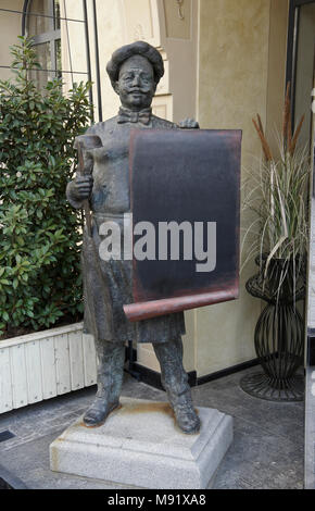 Bronze sculpture of a chef holding a scroll and soup ladle outside a restaurant in Old Town, Tbilisi, Georgia - Stock Photo