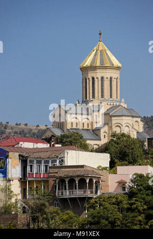 Tsminda Sameba (Holy Trinity) Cathedral on a hill behind old, balconied buildings, Tbilisi, Georgia - Stock Photo