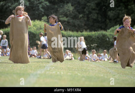 Girls competing in sack race during primary school sports day, England, UK - Stock Photo