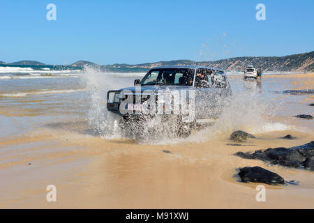 Rainbow Beach, Queensland, Australia - December 23, 2017. 4WD Toyota car driving across a washout in splashes of ocean water on Rainbow Beach in Queen - Stock Photo