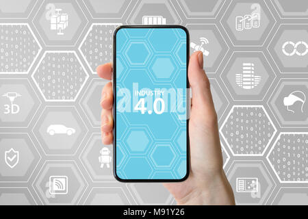 Industry 4.0 text displayed on smartphone screen. Hand holding modern frameless smart phone in front of neutral background. - Stock Photo